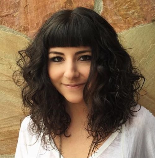 25 medium curly hairstyle with short blunt bangs