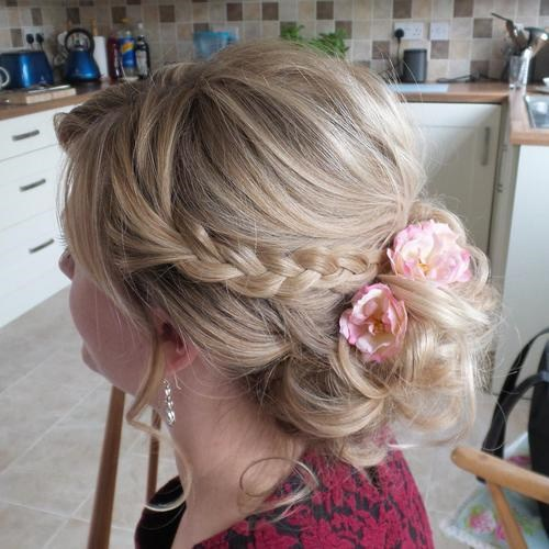 23 low curly updo with braid and flowers